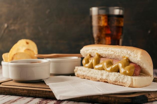Vista normale di un hotdog in primo piano con un bicchiere di coca cola dietro e alcune patatine. concetto di cibo veloce e spazzatura.