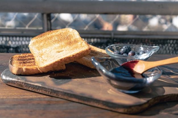 Vista normale di un tavolo con toast, una pentola con marmellata di mirtilli e un'altra pentola con aranadas freschi. concetto di cibo sano.