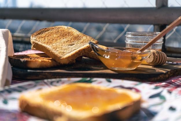 Vista normale di un tavolo con toast, una pentola con marmellata di pesche