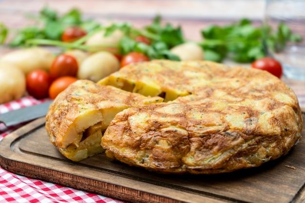 Visualizzazione normale di una tipica frittata di patate spagnola con una porzione separata con patate e pomodorini in un ambiente rustico cucina tradizionale spagnola messa a fuoco selettiva sulla porzione