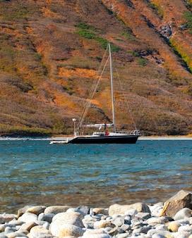 Lo yacht a nord sulla baia dell'oceano pacifico nella penisola di kamchatka con le montagne sullo sfondo