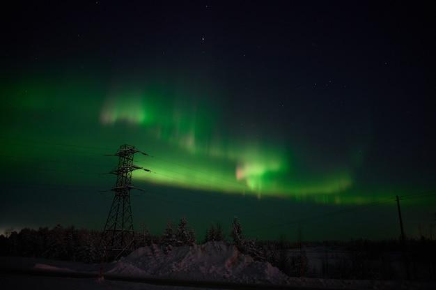Aurora boreale sul campo silenzioso prima del sorgere del sole.