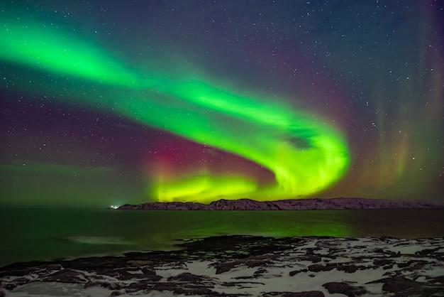 Aurora boreale (aurora boreale) nel cielo sopra il mare di barents