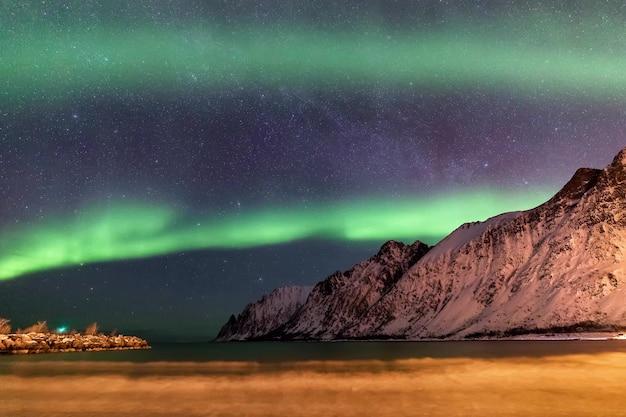 Aurora boreale sopra la spiaggia di ersfjord. bassa marea. isola di senja di notte, norvegia. europa