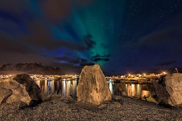Aurora boreale dal punto di vista con rocce in primo piano