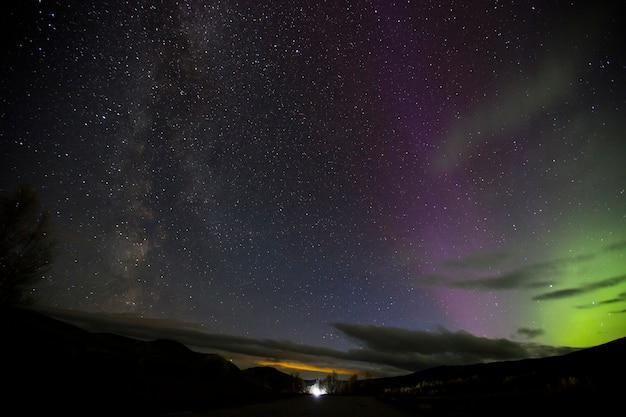 Aurora boreale e via lattea nel parco nazionale di dovrefjell, norvegia. europa