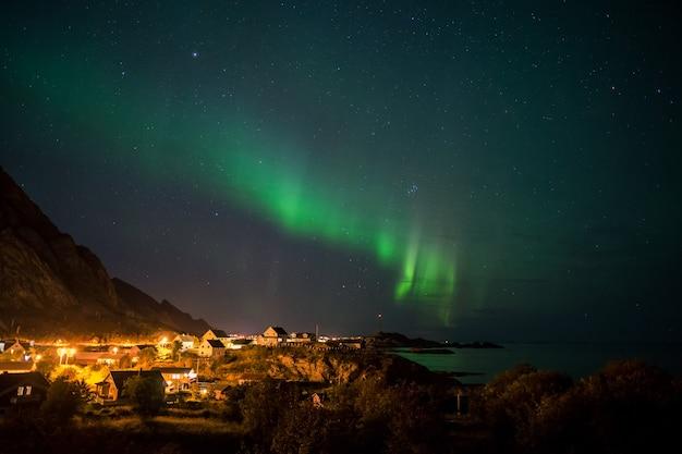 Aurora boreale sopra il piccolo villaggio in lofoten, norvegia