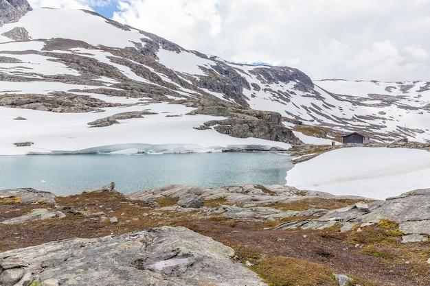 Norvegia montagna, lago, ghiacciaio circondato da nuvole nel riflesso del fiordo norvegese nell'acqua
