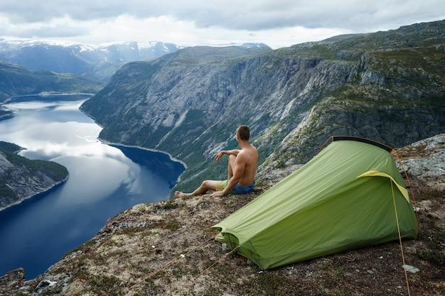 Paesaggio del fiordo norvegese con tenda da campeggio e giovane uomo muscoloso seduto sul bordo della scogliera