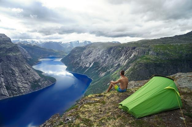 Paesaggio del fiordo norvegese con tenda da campeggio e giovane viaggiatore