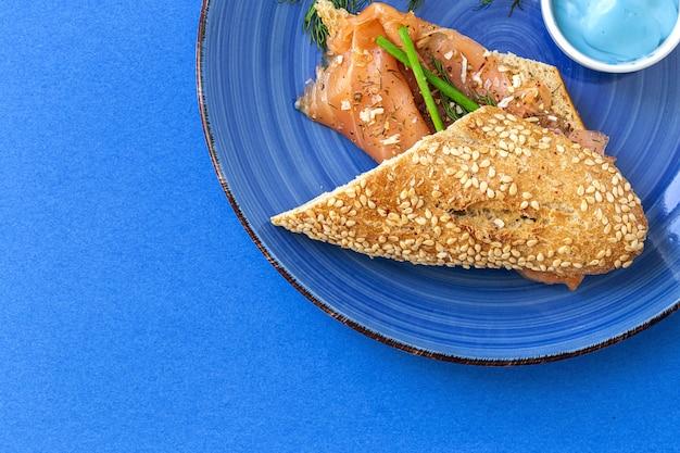 Tartine di salmone affumicato norvegese con limone, salsa di formaggio blu, pepe e sale dall'alto