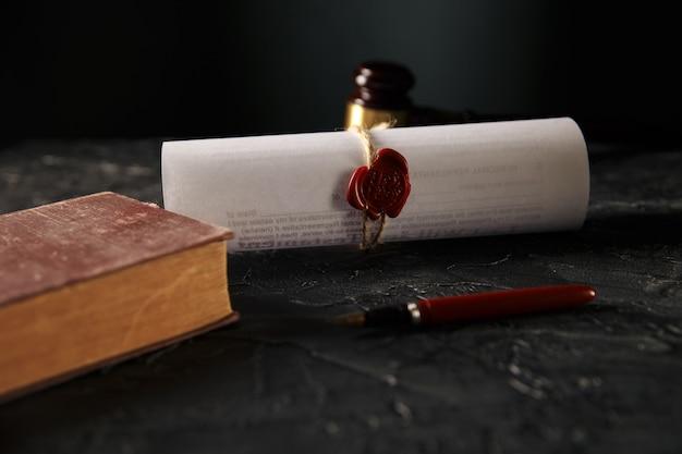 Notaio e nozione di diritto. timbro con libro e penna sul tavolo. martelletto di legno dietro.