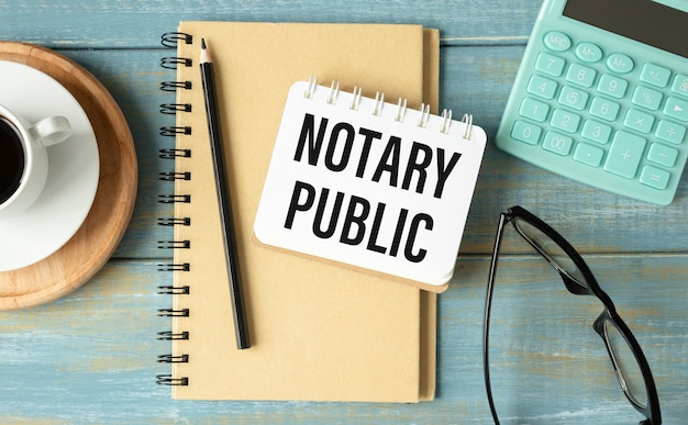 Notaio pubblico è scritto in un blocco note bianco vicino a una calcolatrice, caffè, occhiali e una penna. concetto di affari