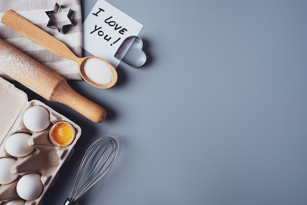Nota ti amo. ingredienti per fare i biscotti fatti in casa su uno sfondo grigio.