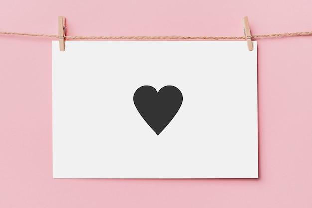 Nota il perno della lettera sulla corda su sfondo rosa, amore e concetto di san valentino con il cuore