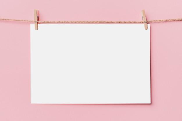 Nota la lettera pin sulla corda su sfondo rosa, amore e concetto di san valentino