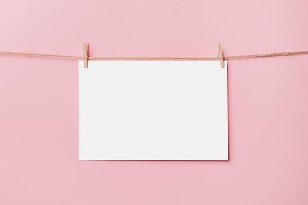 Nota lettera pin sulla corda su sfondo rosa, amore e concetto di san valentino