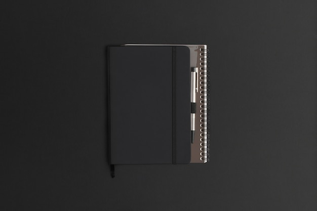 Notebook su sfondo in pelle nera. composizione piatta. vista dall'alto.