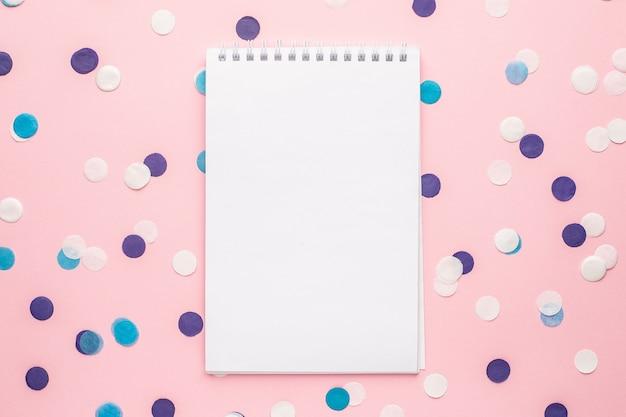 Notebook e coriandoli blu, bianchi e lilla su sfondo di carta di colore rosa vista dall'alto stile minimo
