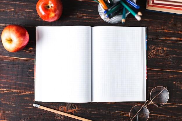 Notebook in una gabbia, matita, mela e bicchieri su un tavolo di legno