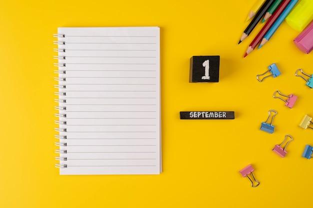 Taccuino e calendario con 1 settembre su sfondo giallo con materiale scolastico vista dall'alto piatta