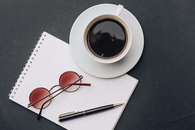 Taccuino e tazza di caffè penna da ufficio e tavolo nero