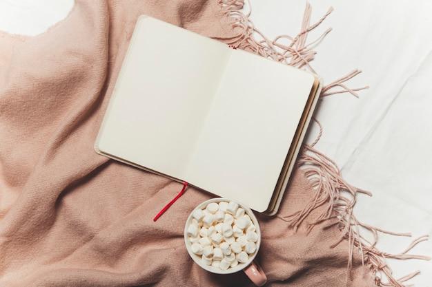 Un quaderno e un caffè con una calda coperta sulla biancheria da letto bianca colazione a letto