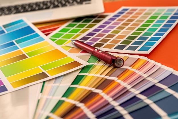 Campioni colorati del taccuino con una penna disposta su uno sfondo arancione. idea di design
