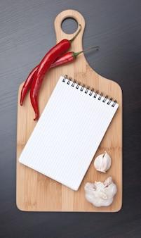 Taccuino per cucinare ricette e peperoncino rosso sul tavolo della cucina