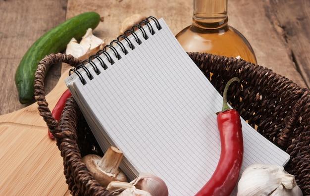 Taccuino per cucinare ricette e verdure su un tagliere