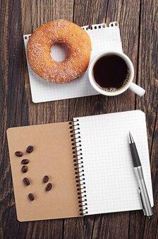 Taccuino e tazza di caffè con ciambella sulla vecchia tavola di legno