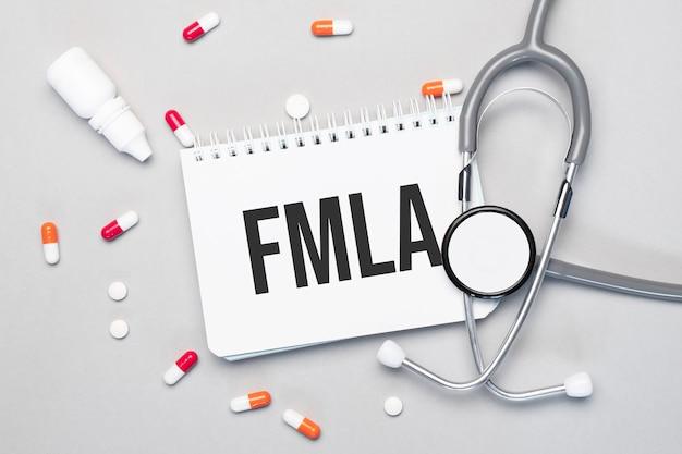 Nel taccuino c'è il testo fmla, accanto a uno stetoscopio, pillole e occhiali.