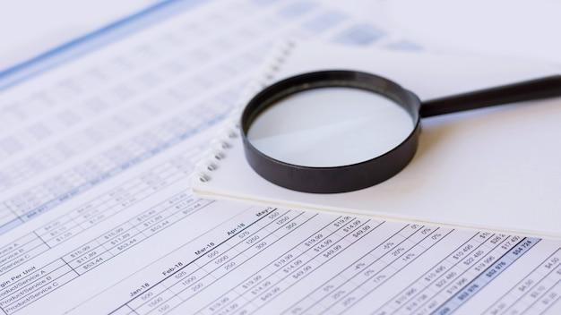 Taccuino e lente d'ingrandimento sopra un documento commerciale