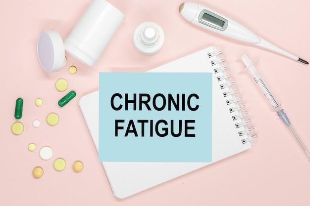 Pagina del taccuino con testo fatica cronica su un tavolo con pillole e siringhe. concetto medico.