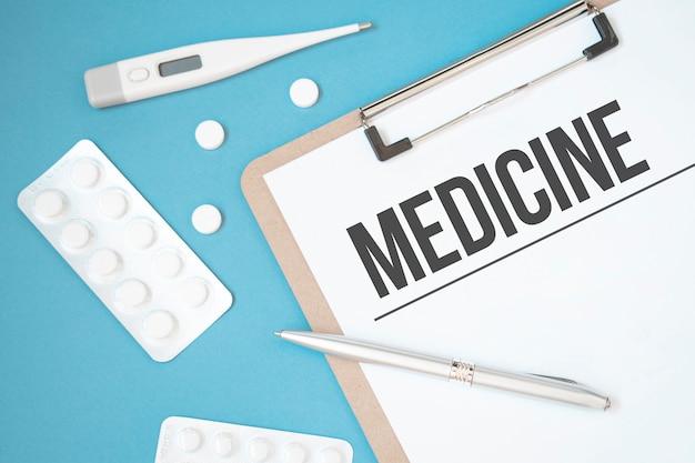 Pagina del taccuino con testo medicina su un tavolo con pillole e matita, concetto medico, vista dall'alto