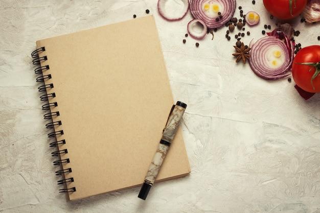 Taccuino, penna, tagliere e verdure su uno sfondo chiaro.