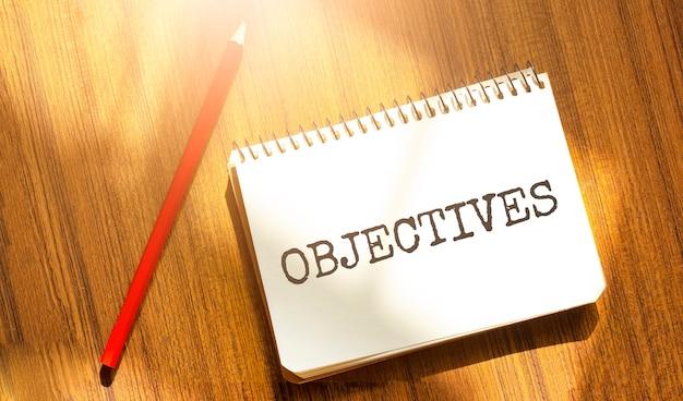Notebook e penna su un tavolo di legno, copia spazio per testo, iscrizione obiettivi su carta gialla sgualcita, luogo di lavoro, brainstorming