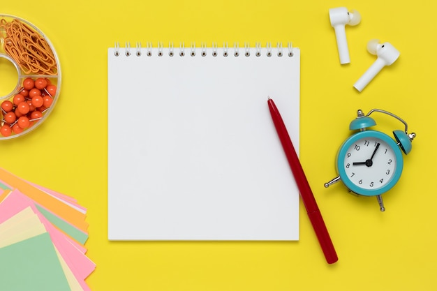 Taccuino e penna su uno sfondo giallo. blocco note, cuffie bianche, sveglia, clip e adesivi colorati sul posto di lavoro.