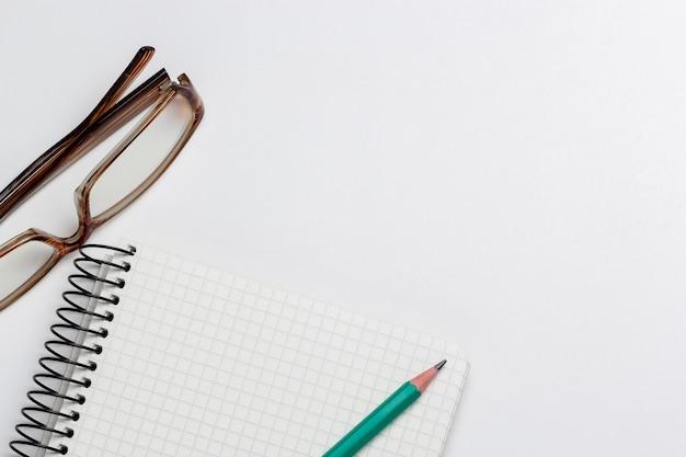Taccuino, matita e bicchieri su sfondo bianco isolato