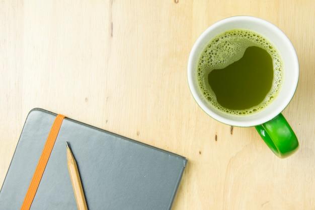 Taccuino e matita con greentea su fondo di legno. vista dall'alto, concetto di posa piatta.