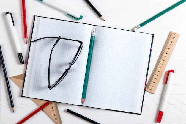 Taccuino, matite, righelli, occhiali, pennarelli sul tavolo bianco, copia spazio.