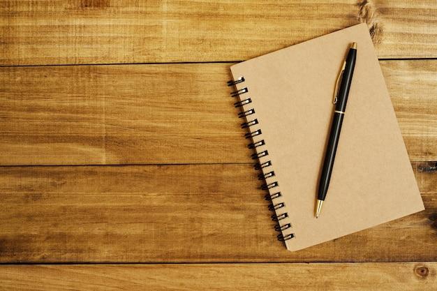 Taccuino posizionato su un pavimento di legno marrone e una penna