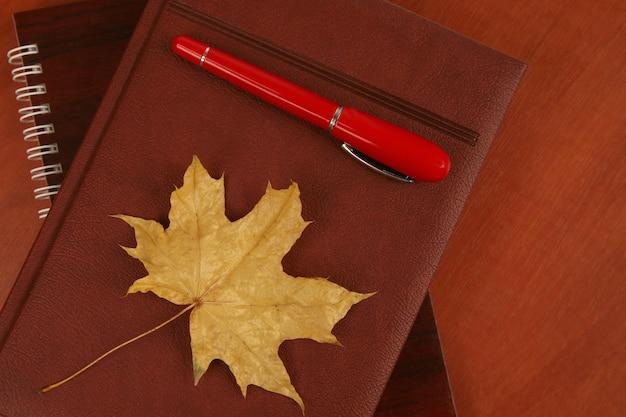 Il taccuino e la penna rossa con foglia d'autunno sdraiati su un tavolo di legno
