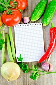 Taccuino, pomodori rossi, peperoncino rosso, prezzemolo, aglio, cipolla, cetriolo, baccelli di fagiolini su una vecchia tavola di legno
