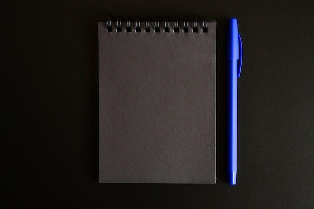 Taccuino su una molla con fogli neri e una penna blu su sfondo nero.