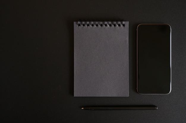 Notebook su una molla con fogli neri e una penna e telefono cellulare su uno sfondo nero.