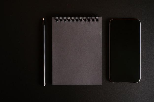 Taccuino su una molla con fogli neri e una penna e telefono cellulare sul nero