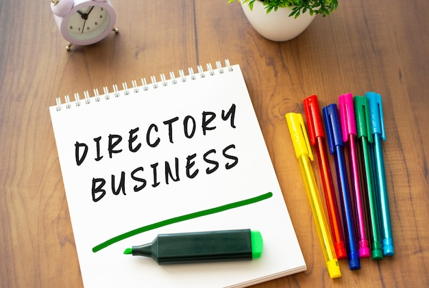 Un taccuino su una molla con il testo directory business su un foglio bianco si trova su un tavolo in legno marrone con penne colorate. concetto di affari.