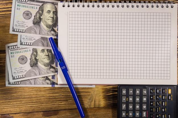 Taccuino con dollari, penna e calcolatrice sulla scrivania in legno. concetto finanziario