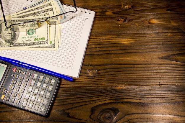 Taccuino con dollari, penna, occhiali e calcolatrice sulla scrivania in legno. concetto finanziario